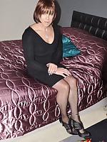 A sexy looking TGirl waits on a satin sheet covered bed for some company.